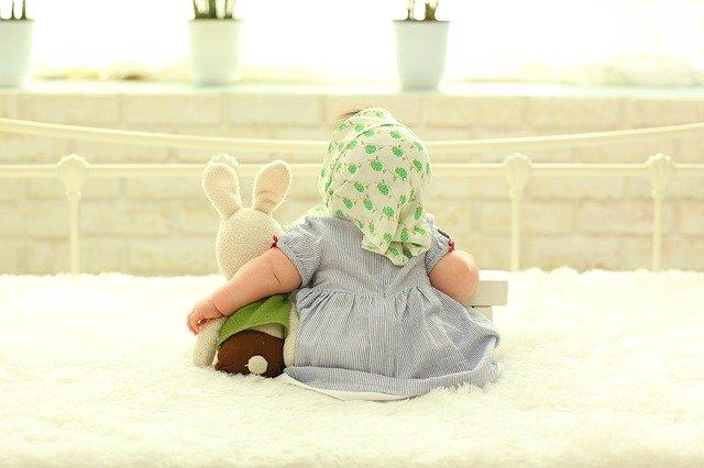 Bábätko v šatách a šatke na hlave sedí na posteli s plyšovým zajacom.jpg