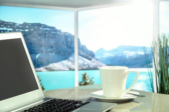 Notebook, šálka kávy, okná, výhľad na more.jpg