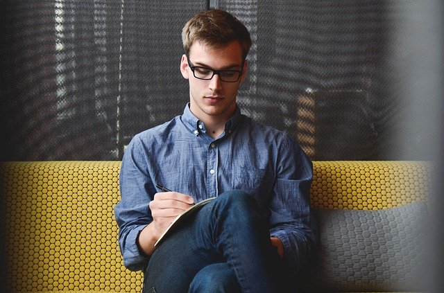 Muž sedí na sedačke a píše do zápisníku